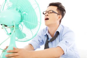man with fan needs air conditioning repair in Tomball TX